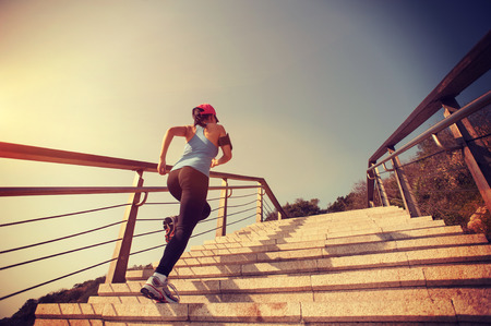 woman running: healthy lifestyle sports woman running up on stone stairs sunrise seaside