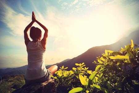 young yoga woman at sunrise mountain peak Imagens
