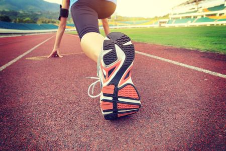 escarpines: corredor joven mujer está preparando para una carrera en la pista