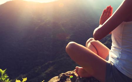 sol radiante: Yoga de la mujer joven en el pico de la monta�a la salida del sol