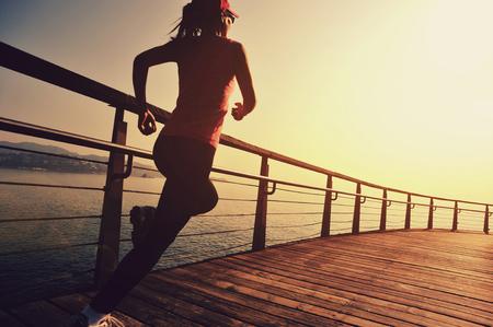 jeune femme de sports de remise en forme en cours d'exécution sur bois promenade le lever du soleil mer