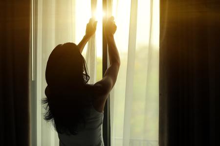 chambre � coucher: jeune femme ouverture des rideaux dans une chambre Banque d'images