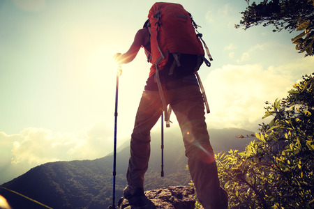hiking: woman backpacker enjoy the view at mountain peak cliff