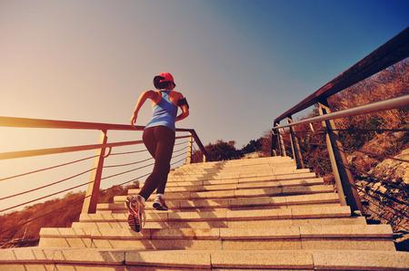gesunden Lebensstil Sport Frau auf Steintreppen Sonnenaufgang am Meer gelaufen