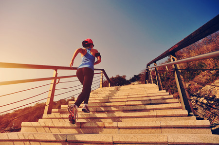 morning sunrise: healthy lifestyle sports woman running up on stone stairs sunrise seaside