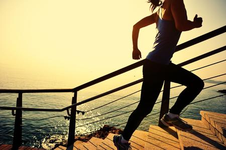 生活方式: 健康的生活方式,運動的女人在石階日出海邊跑起來