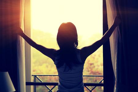 cielos abiertos: Mujer joven que abre las cortinas en un dormitorio Foto de archivo