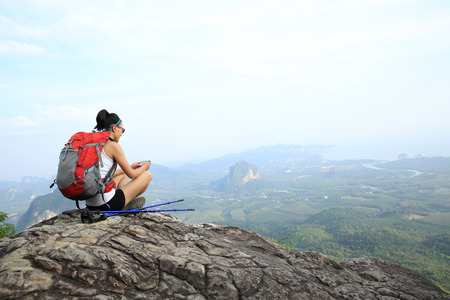 hiking boot: young woman hiker taking photo with smart phone at mountain peak