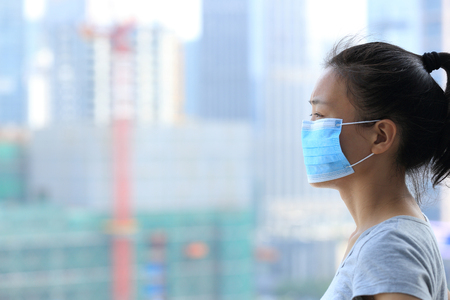 mascarilla: mujer asi�tica usar mascarilla en la ciudad de la contaminaci�n Foto de archivo