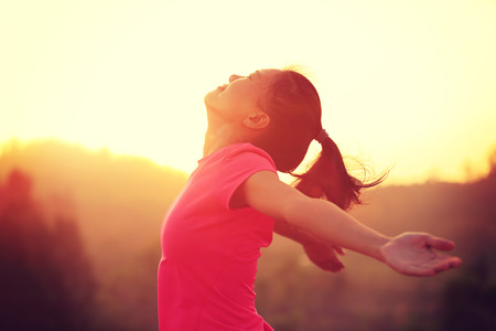 cheering young asian woman open arms at sunrise mountain peak Stock Photo
