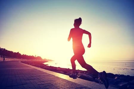personas trotando: Runner atleta que corre en la playa. Aptitud de la mujer silueta de la salida del sol para correr entrenamiento concepto de bienestar. Foto de archivo