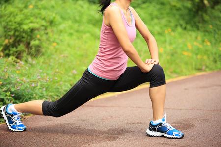ヘルシー アジアの女性ランナーを実行する前に足を伸ばし