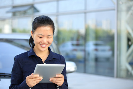 tablet: beautiful asian businesswoman use digital tablet leaning on car outside of modern office building