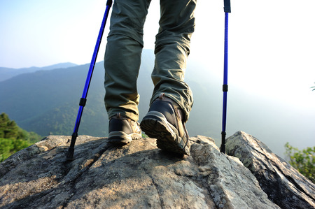 hiker stand on mountain peak rock