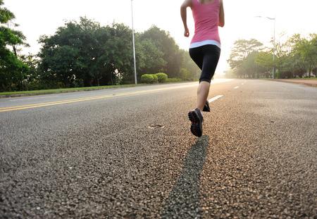 atleta corriendo: Runner atleta correr en la carretera. fitness mujer amanecer trotar entrenamiento concepto de bienestar.
