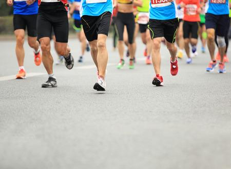 marathon running: Unidentified marathon athletes legs running on city road