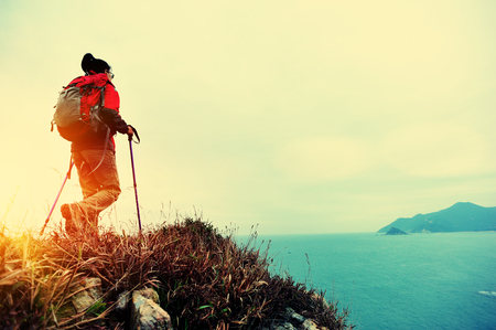 hiking boots: woman hiker hiking on seaside trail Stock Photo