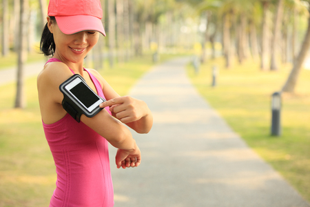 mp3 player: Runner athlete set the cellphone mp3 player at tropical park. woman fitness jogging workout wellness concept.