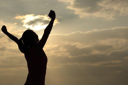 silueta humana: mujer brazos abiertos bajo el sol en la playa