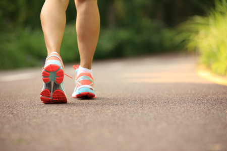 training shoes: young fitness woman legs running at forest trail