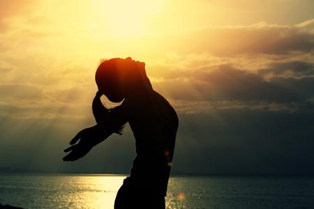 femme bras ouverts sous le lever du soleil au bord de la mer