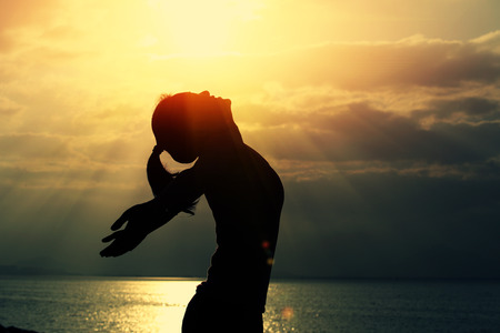 vrouw open armen in het kader van de zonsopgang bij kust