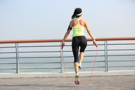 saltar la cuerda: aptitud de la mujer joven saltando la cuerda en la playa