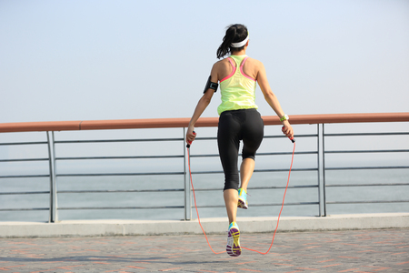 woman rope: young fitness woman jumping rope at seaside Stock Photo