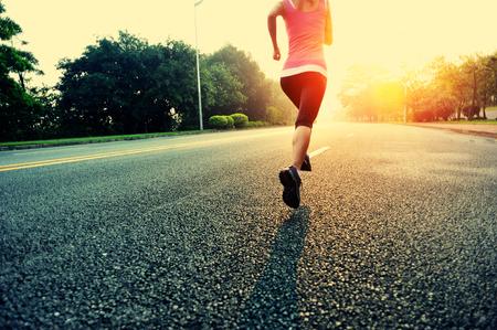 jogging shoes: woman running at road.