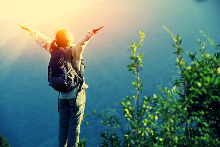nature: cheering woman hiker open arms at mountain peak Stock Photo