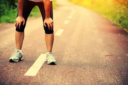 agotado: Corredor de la mujer cansada de tomar un descanso después de correr duro en el camino del campo. atleta sudoroso después del entrenamiento de maratón en la carretera nacional.