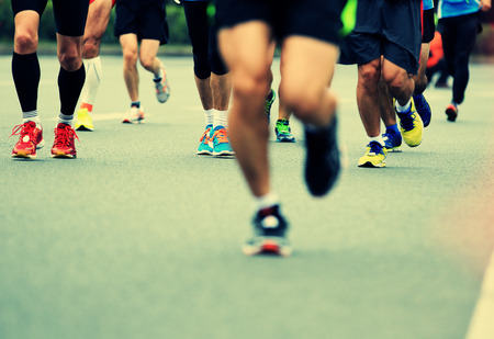 outdoor sport: marathon athlete legs running on city road