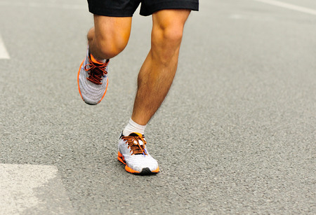 man exercise: Unidentified marathon athlete legs running on city road