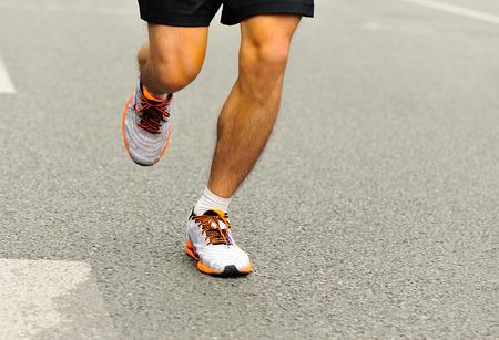 exercise man: Unidentified marathon athlete legs running on city road