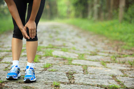 dolor de rodilla: woman runner hold her sports injured knee Foto de archivo