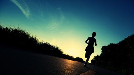 marathon runner: young woman runner running on sunrise seaside
