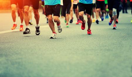 piernas hombre: atleta de maratón que se ejecuta en camino de ciudad