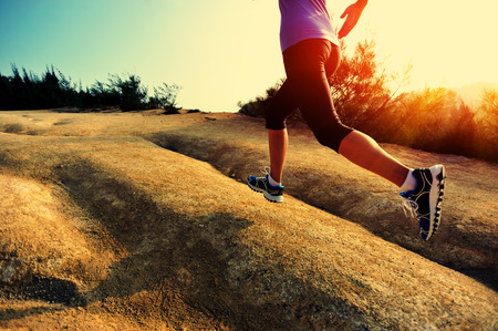 trail: young woman runner running on seaside mountain trail