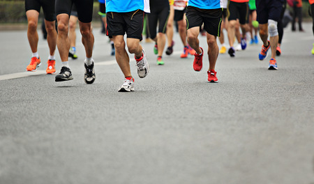 marathon athlete running on city road Stock Photo