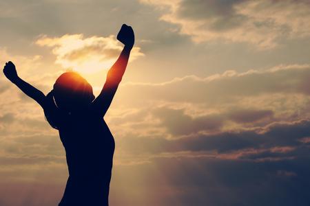 vrouwen: vrouw open armen in het kader van de zonsopgang bij kust Stockfoto