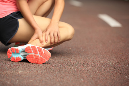 calves: woman runner hold her twisted ankle