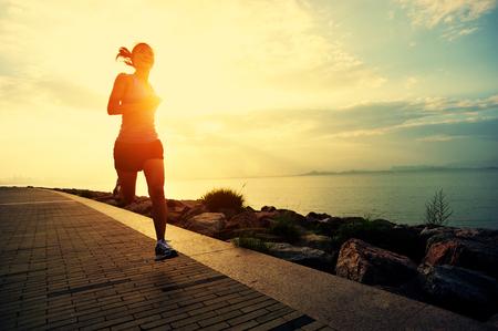 健身: 亞軍運動員在海邊運行。女人健身剪影日出慢跑鍛煉健康概念。