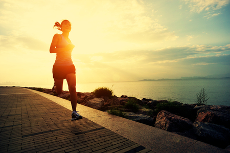 motion: Löpare idrottsman som kör på havet. kvinna fitness silhuett soluppgång jogging träning wellness koncept. Stockfoto