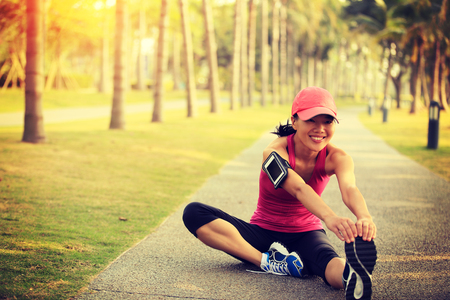 girl in a hat: woman runner stretching legs outdoor