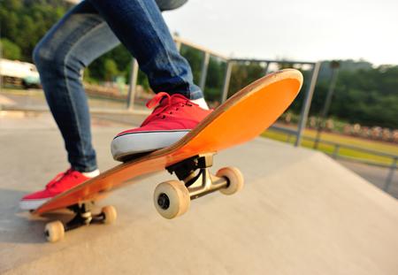 jonge vrouw benen skateboarden op skatepark Stockfoto