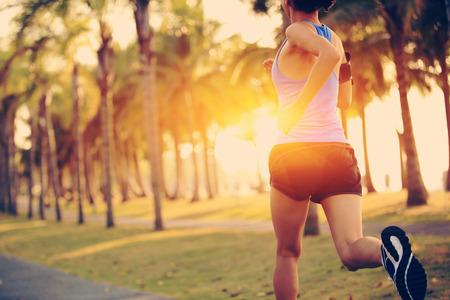 running: woman running at tropical park.