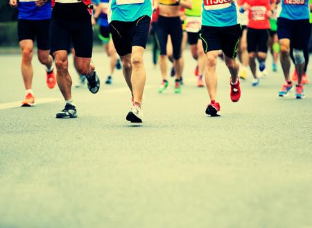 personas corriendo: Marat�n de carrera a pie, la gente los pies en el camino de ciudad