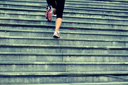 femme sport jambes qui courent dans les escaliers en pierre Banque d'images