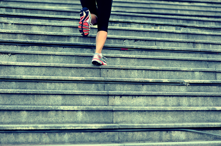 woman stairs: sports woman legs running up on stone stairs Stock Photo