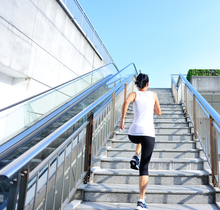 woman stairs: Runner athlete running on stairs. woman fitness jogging workout wellness concept.
